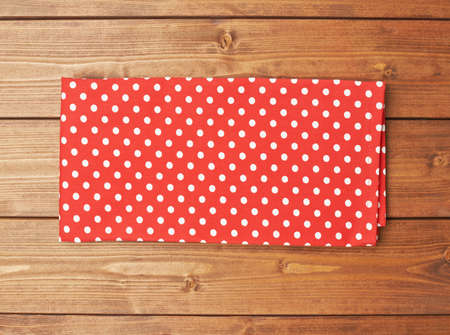 table surface: Red polka dot tablecloth or towel over the surface of a brown wooden table Stock Photo