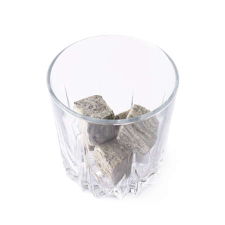 tumbler glass: Empty whiskey tumbler glass filled with cooling granite stones isolated over the white  Stock Photo