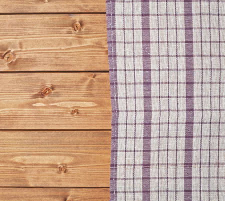 table surface: Violet tablecloth or towel over the surface of a brown wooden table