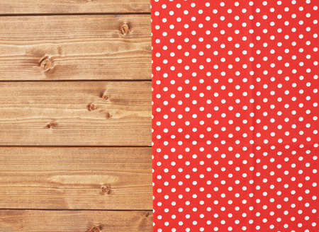 dot surface: Red polka dot tablecloth or towel over the surface of a brown wooden table Stock Photo