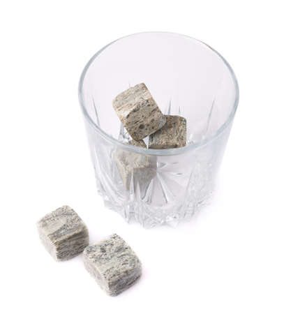 tumbler glass: Empty whiskey tumbler glass filled with cooling granite stones isolated over the white background