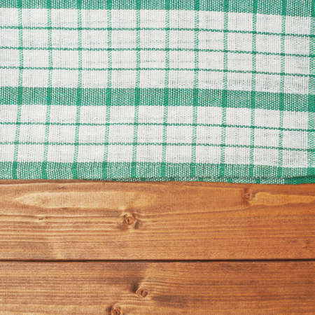Green tablecloth or towel over the surface of a brown wooden table photo