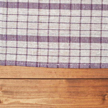 Violet tablecloth or towel over the surface of a brown wooden table photo