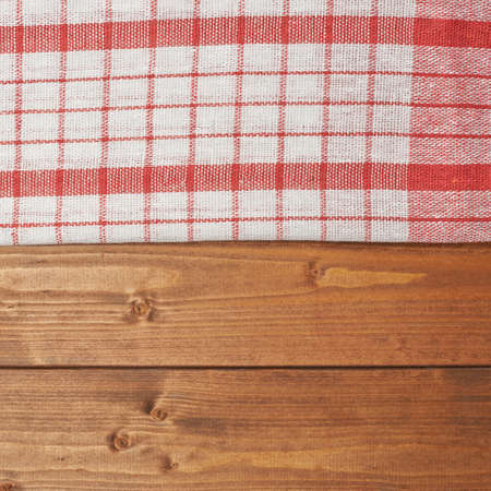 table surface: Red tablecloth or towel over the surface of a brown wooden table
