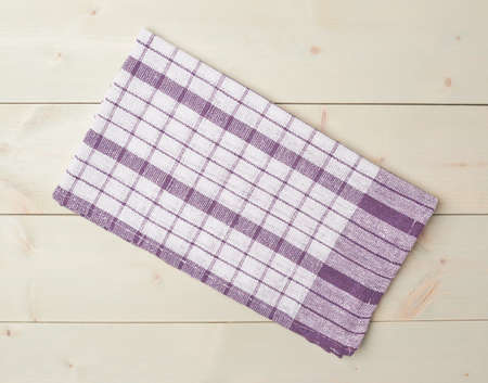table surface: Violet squared tablecloth or towel over the surface of a wooden table Stock Photo