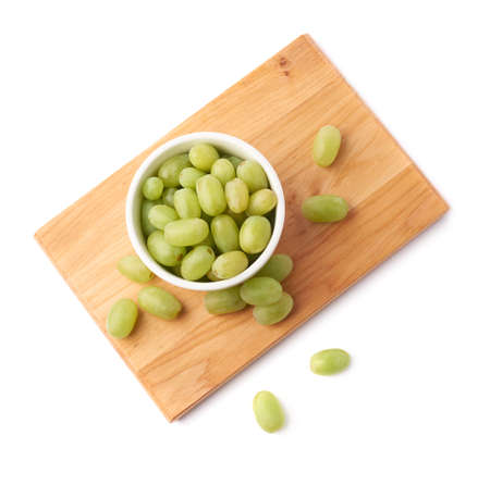 White table grapes in a ceramic bowl over the serving wooden board, composition isolated over the white background Standard-Bild