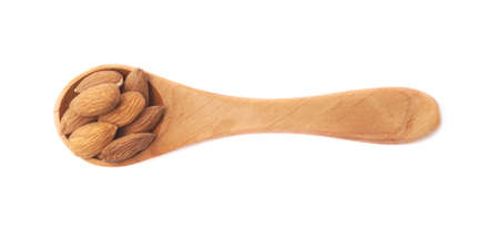 measuring spoon: Small wooden measuring spoon full of almond seeds isolated over the white background Stock Photo