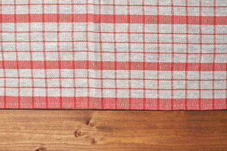Red tablecloth or towel over the surface of a brown wooden table photo