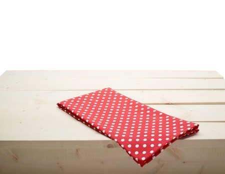 table surface: Red polka dot tablecloth or towel over the surface of a wooden table, composition isolated against the white background