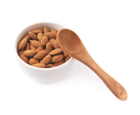 measuring spoon: Ceramic white bowl full of almond seeds and wooden measuring spoon, composition isolated over the white background