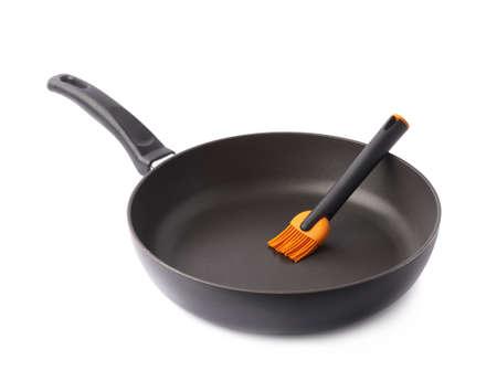 ustensiles de cuisine: Brosse huile de silicone dans une poêle noire, la composition isolé sur fond blanc