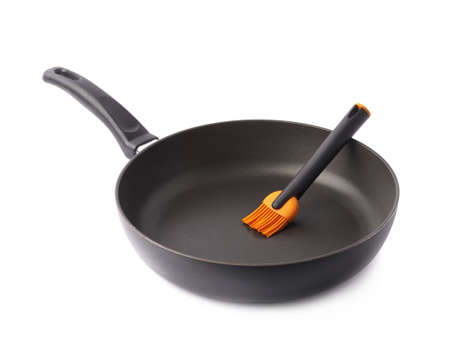 kitchenware: Silicone oil brush in a black frying pan, composition isolated over the white background
