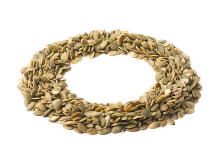 Round frame made of multiple pumpkin seeds, composition isolated over the white background photo