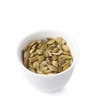 White ceramic cup bowl filled with multiple pumpkin seed snacks, composition isolated over the white background photo