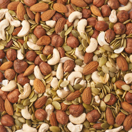 Surface covered with multiple different nuts and seeds as a background composition texture Stock Photo
