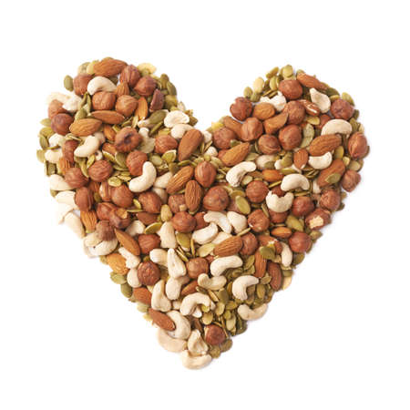 Heart shape made of multiple different nuts and seeds mix, composition isolated over the white background