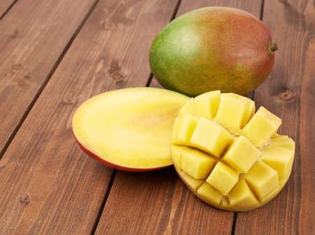 mango fruta: Fruta madura de mango que miente sobre la superficie del tablero de madera de color marr�n como fondo de la composici�n