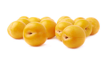 Pile of multiple yellow mirabelle plums isolated over the white background photo