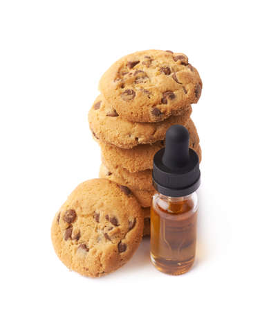 essence: Oil essence in a glass bottle next to the pile of cookies isolated over the white background