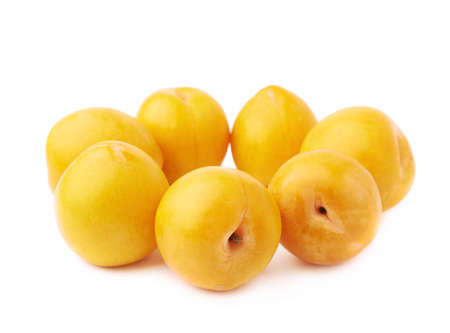 Yellow mirabelle plums aligned in circle, composition isolated over the white background photo