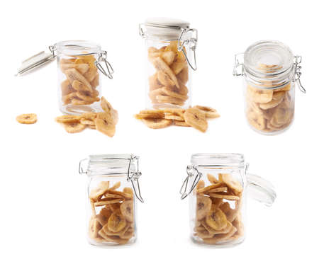Glass jar filled with the dried banana snack slices, composition isolated over the white background photo
