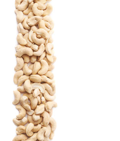 Multiple cashew nuts aligned in a line as a copyspace background composition isolated over the white background Banco de Imagens