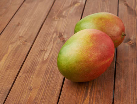 mango: Ripe mango fruit lying over the brown colored wooden board surface