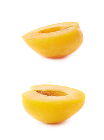 Cut open half of a yellow mirabelle plum isolated over the white background, set of two different foreshortenings photo
