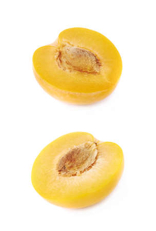 Cut open half of a yellow mirabelle plum isolated over the white background photo