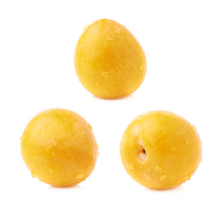 Single yellow mirabelle plum covered with the drops of water, isolated over the white background photo