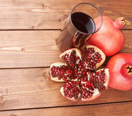 punica granatum: Pomegranate Punica granatum fruit next to the tall glass full of red juice, composition placed over the wooden boards surface
