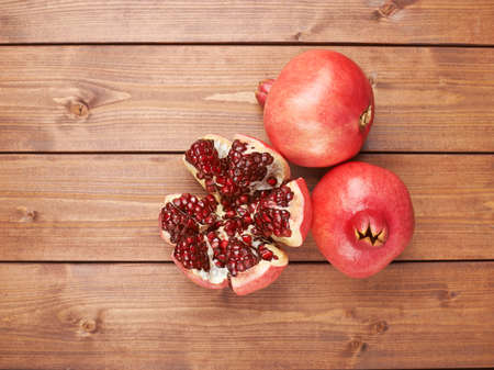 granatum: Pomegranate Punica granatum fruit composition placed over the wooden boards surface