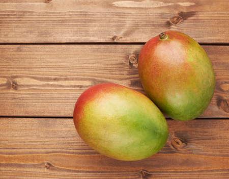 Rijpe mango vruchten liegen over de bruin gekleurde houten plank oppervlak als achtergrond samenstelling