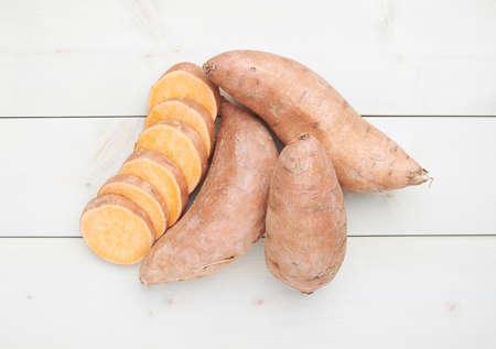 batata: Camote o Ipomoea batatas composición sobre la superficie de madera tableros blanco Foto de archivo