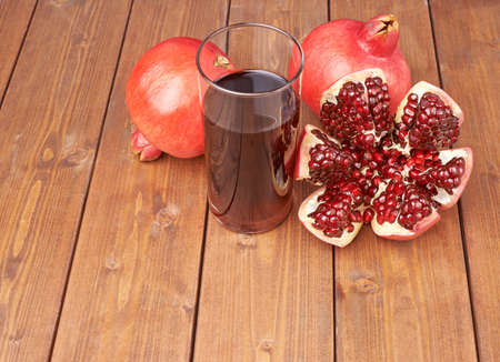 granatum: Pomegranate Punica granatum fruit next to the tall glass full of red juice, composition placed over the wooden boards surface