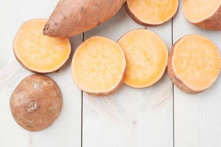 papas: Camote o Ipomoea batatas composición sobre la superficie de madera tableros blanco Foto de archivo