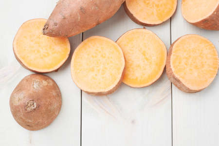 sweet segments: Sweet potato or Ipomoea batatas composition over the white wooden boards surface