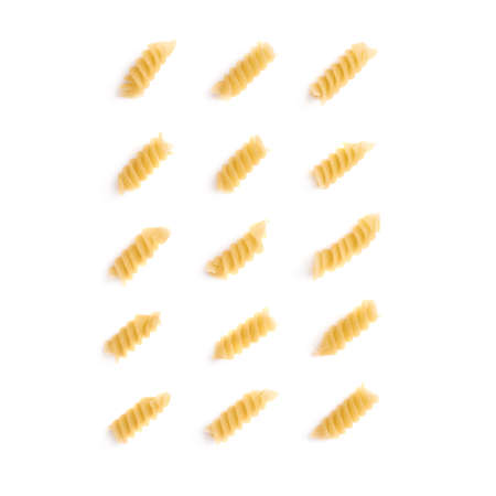 rotini: Single pieces of dry rotini yellow pasta over isolated white background