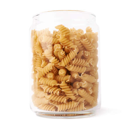 twists: Glass jar filled with dry rotini yellow pasta over isolated white background Stock Photo