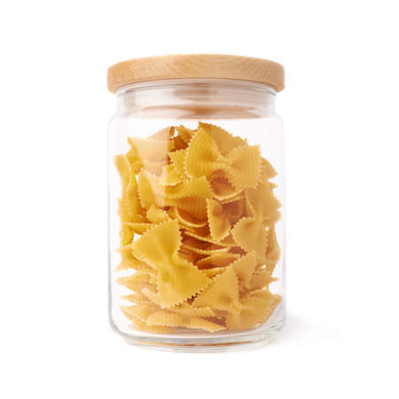 a jar stand: Glass jar filled with dry farfalle yellow pasta over isolated white background