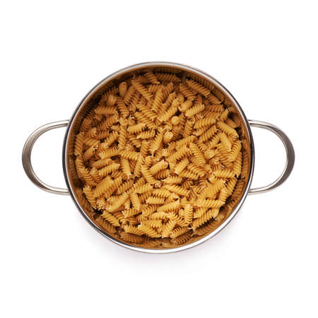 rotini: Metal pan filled with dry rotini yellow pasta over isolated white background Stock Photo