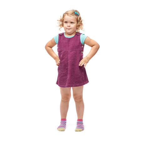 questioned: Young little girl with curly hair and arms on hips in purple dress standing over isolated white background