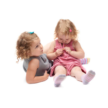 keek: Couple of young little girls sisters with curly hair in gray and pink dress sitting over isolated white background Stock Photo