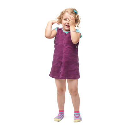 indignant: Young indignant little girl with curly hair in purple dress standing over isolated white background
