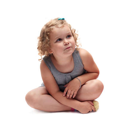 questioned: Young little girl with curly hair in gray dress sitting over isolated white background