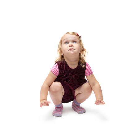 questioned: Young little girl with curly hair in purple dress sitting over isolated white background Stock Photo