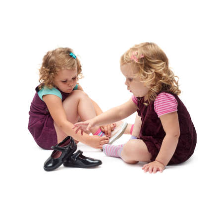 purple shoes: Couple of young little girls sisters with curly hair in purple dress sitting and putting shoes over isolated white background