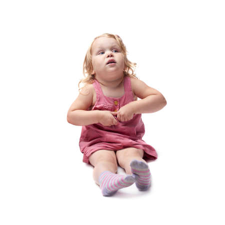 questioned: Young little girl with curly hair in pink dress sitting over isolated white background