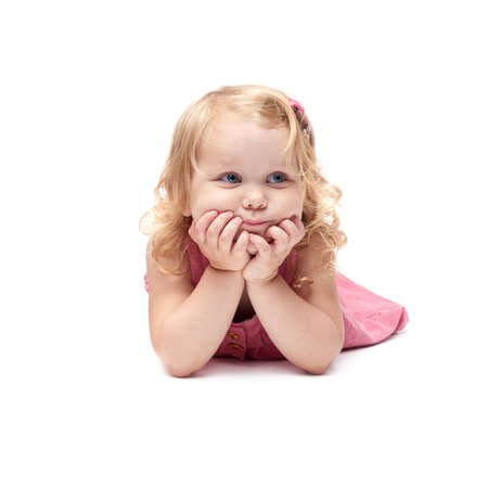 questioned: Young little girl with curly hair in pink dress lying over isolated white background