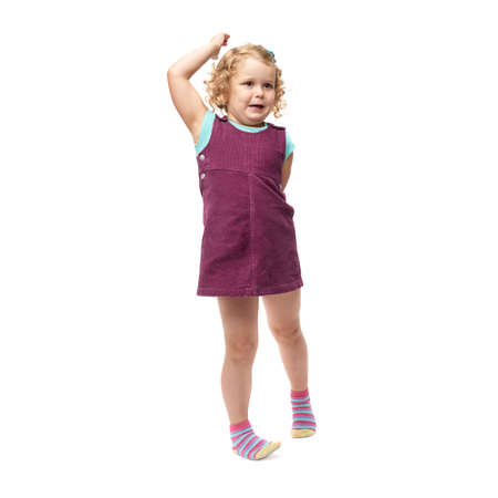 indignant: Young little indignant girl with curly hair in purple dress standing over isolated white background